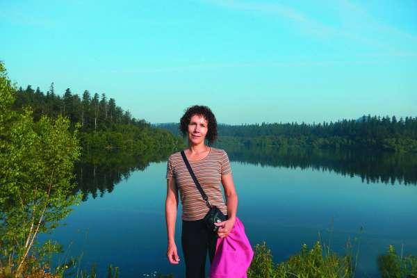 Mag. Nika Munih. V ozadju dobro vidni fraktali v naravi: jezero, gozd, odsevi v jezeru.